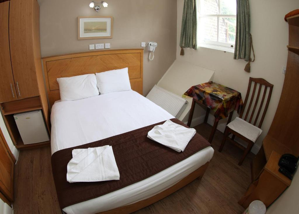A bed or beds in a room at Kensington Suite Hotel