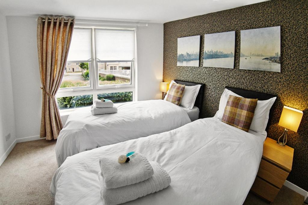 A bed or beds in a room at Thistle Apartments - King's Apartment