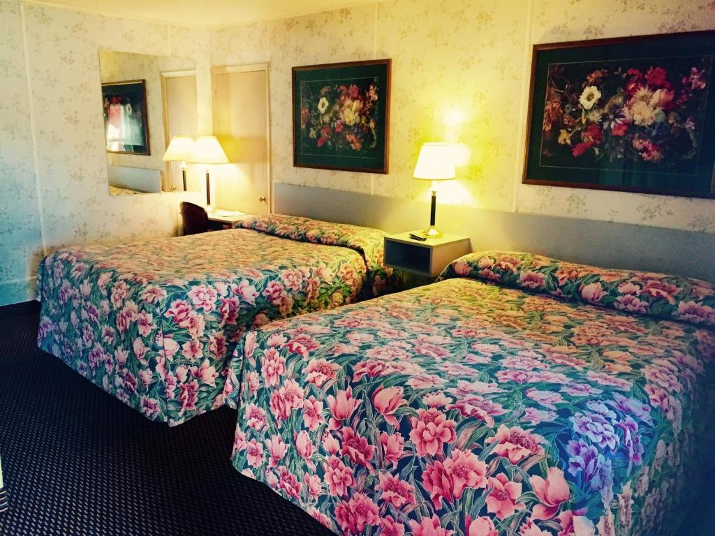 A bed or beds in a room at Travelers Inn Motel