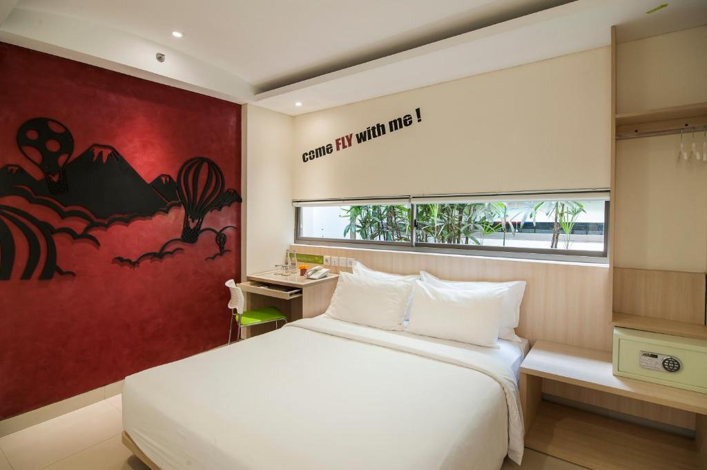 A bed or beds in a room at Grandmas Plus Hotel Legian