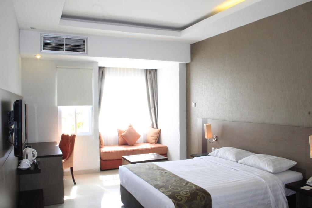 A bed or beds in a room at Lorin New Kuta Hotel