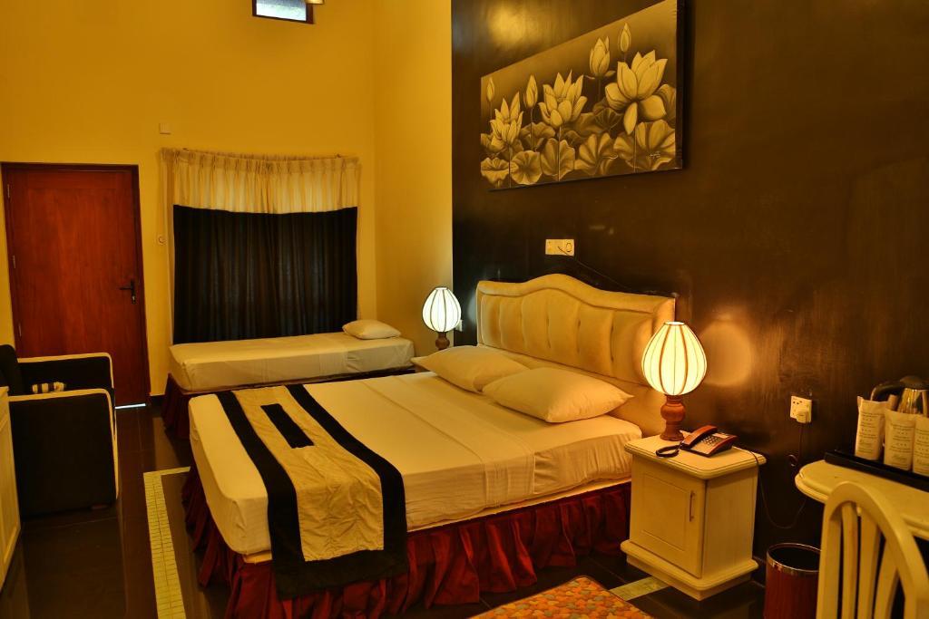 A bed or beds in a room at Miridiya Lake Resort