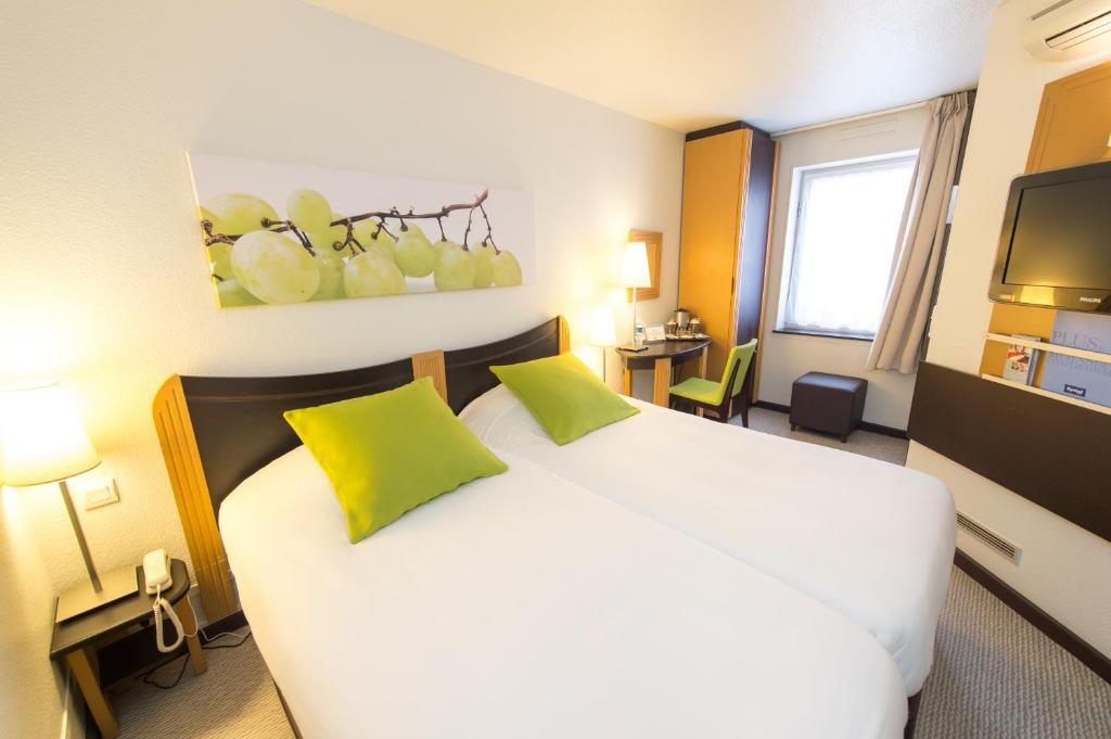 A bed or beds in a room at Kyriad Villefranche Sur Saone