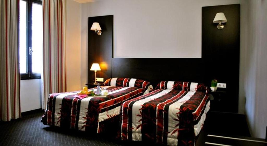A bed or beds in a room at Hôtel Alliance