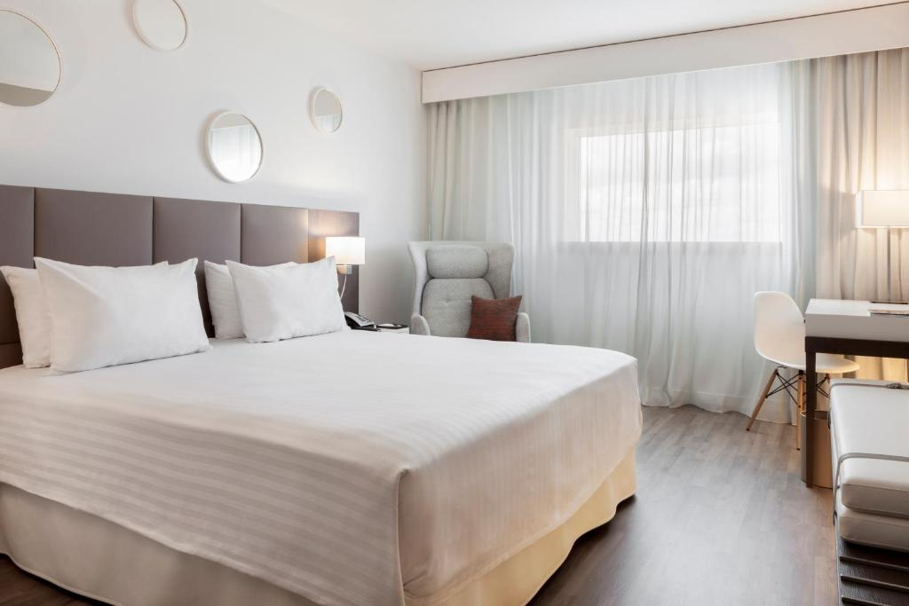 A bed or beds in a room at AC Hotel Paris Le Bourget Airport by Marriott