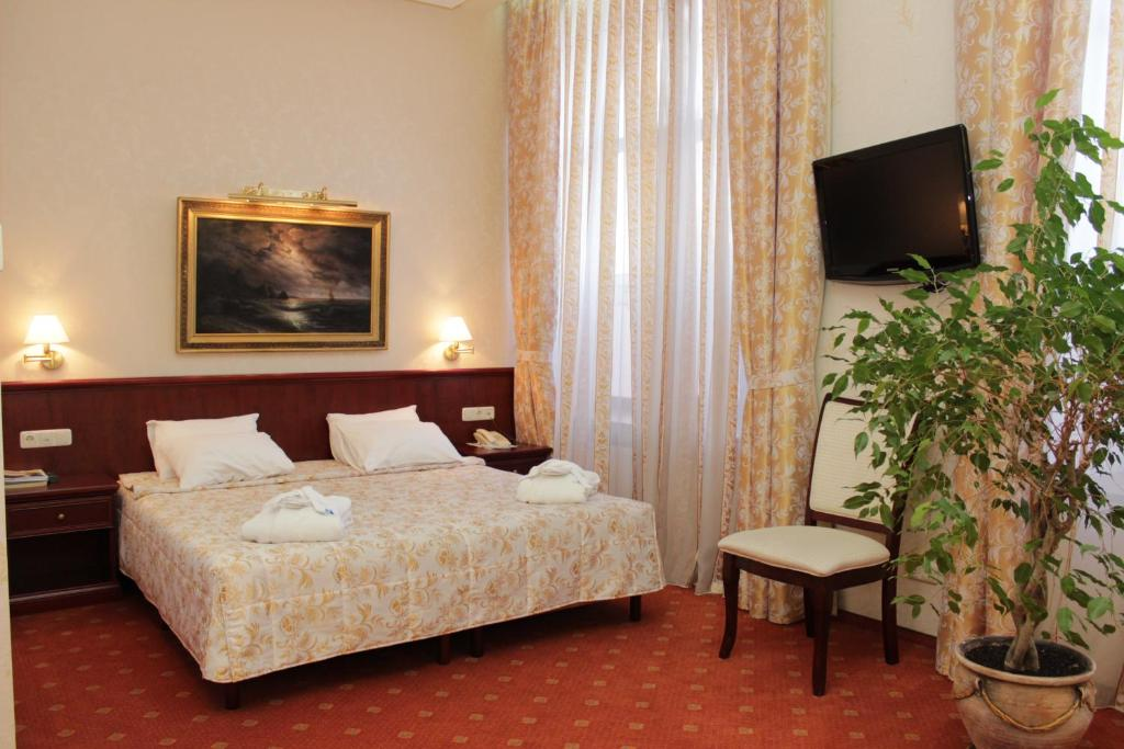 A bed or beds in a room at Dnepr Hotel