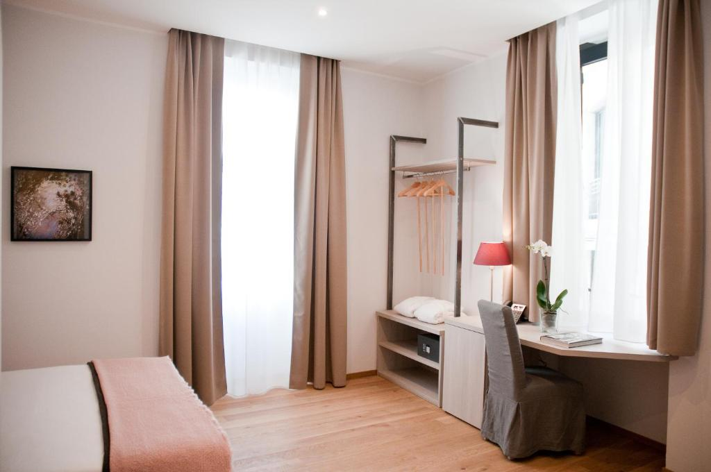 A bed or beds in a room at Giuturna Boutique Hotel