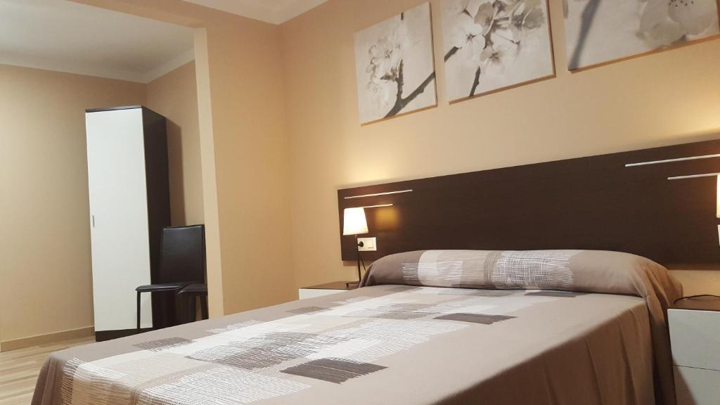 A bed or beds in a room at Pensión Avenida