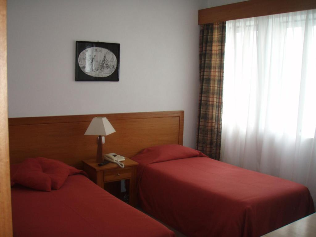 A bed or beds in a room at Hotel Residencial Ermida dos Remédios