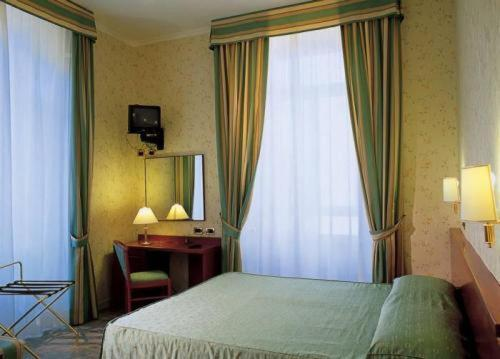 A bed or beds in a room at Hotel Dina
