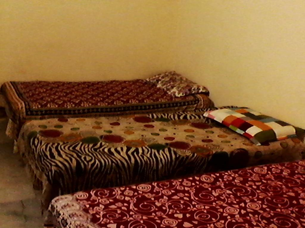 A bed or beds in a room at Indu Dormitory and Guest House