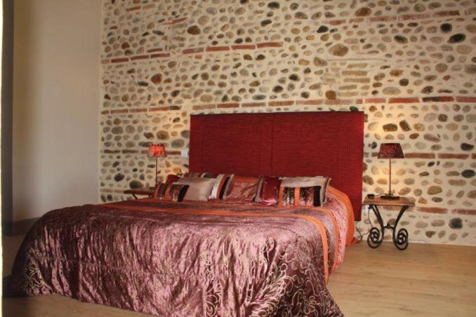 A bed or beds in a room at Terre de Garance