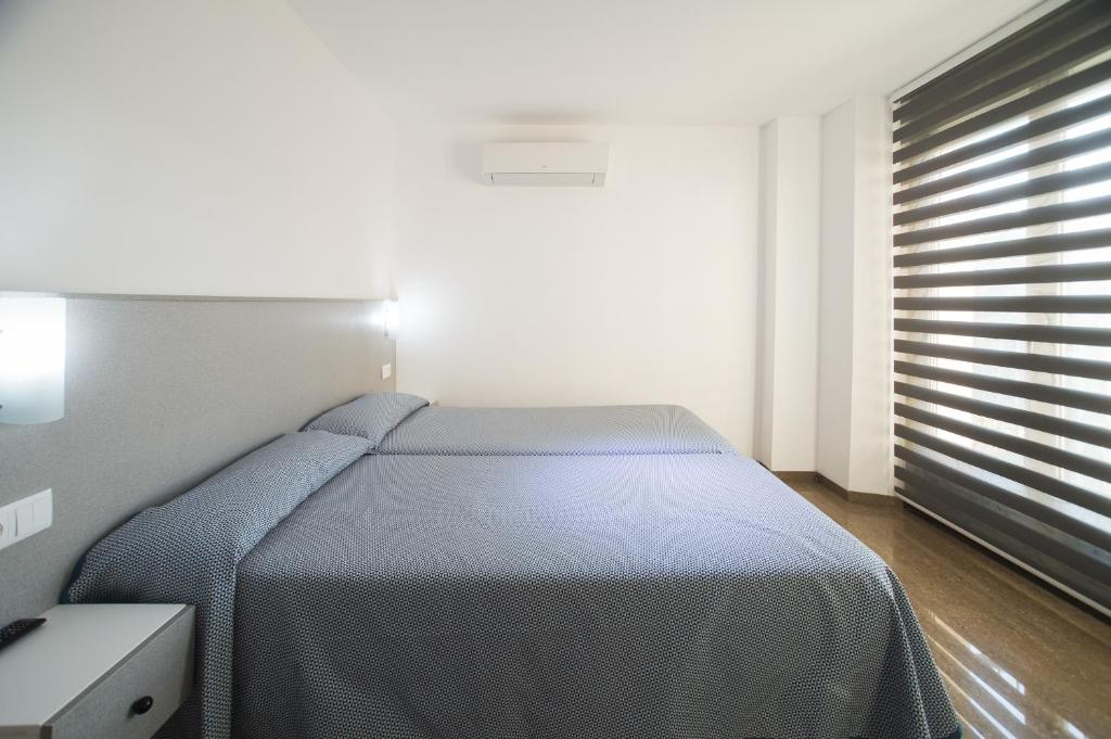 A bed or beds in a room at Hostal Drassanes