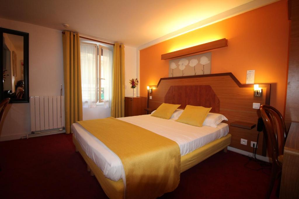 A bed or beds in a room at Le Nouvel Hôtel du Théâtre
