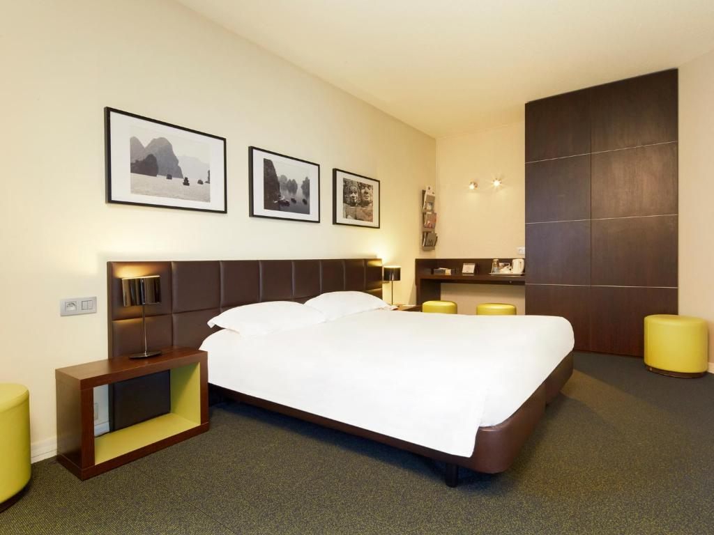A bed or beds in a room at Kyriad Hôtel Orly Aéroport - Athis Mons