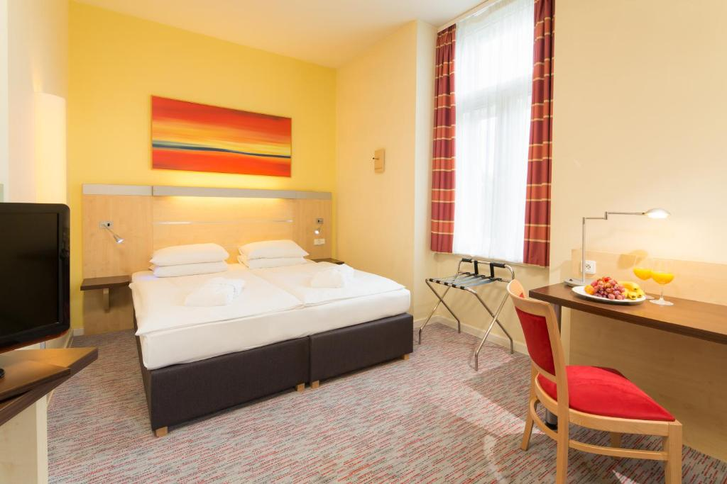 A bed or beds in a room at Exe City Park Hotel