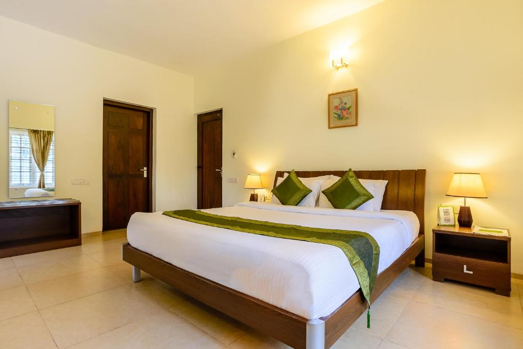A bed or beds in a room at Treebo Trend Oleander Serviced Apartments Coorg