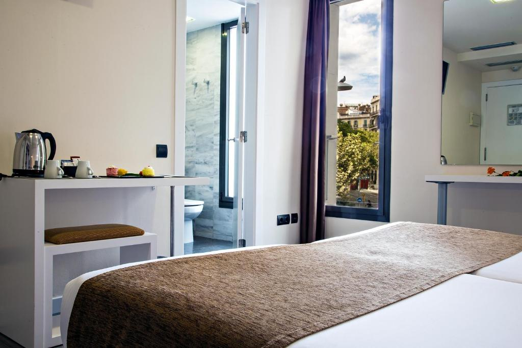 A bed or beds in a room at BCN Urban Hotels Del Comte