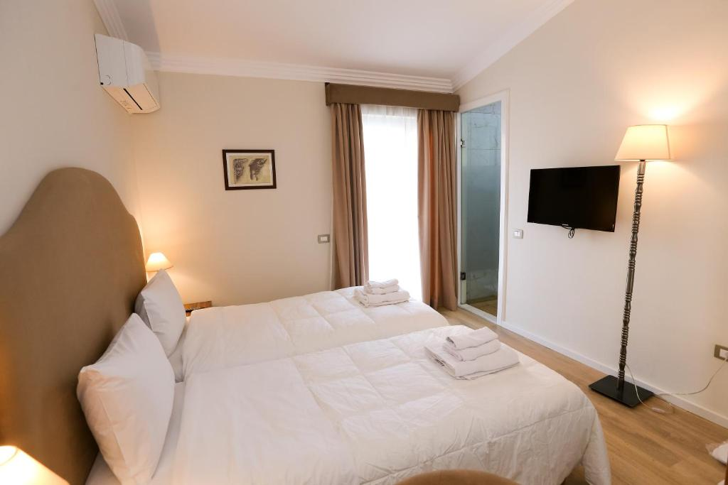 A bed or beds in a room at Hotel Hermes Tirana