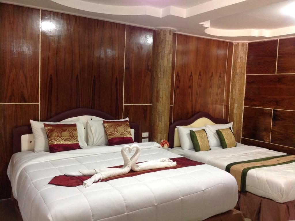 En eller flere senge i et værelse på Ruan Mai Naiyang Beach Resort