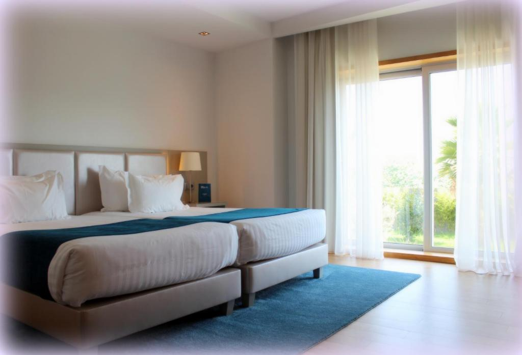 A bed or beds in a room at OPOHOTEL Porto Aeroporto