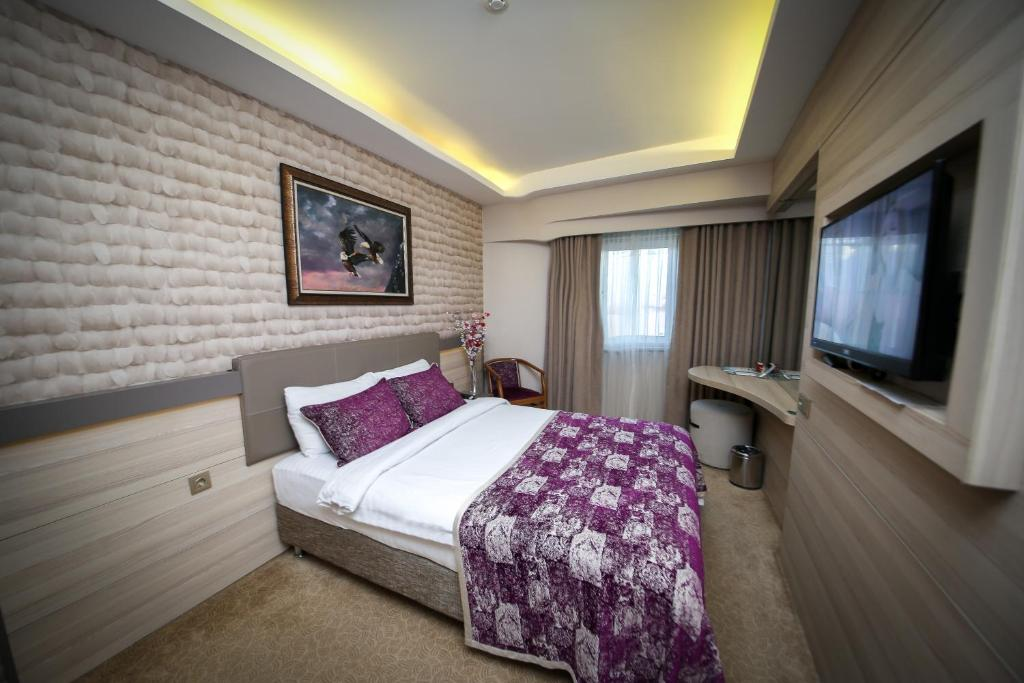 A bed or beds in a room at Asya Hotel
