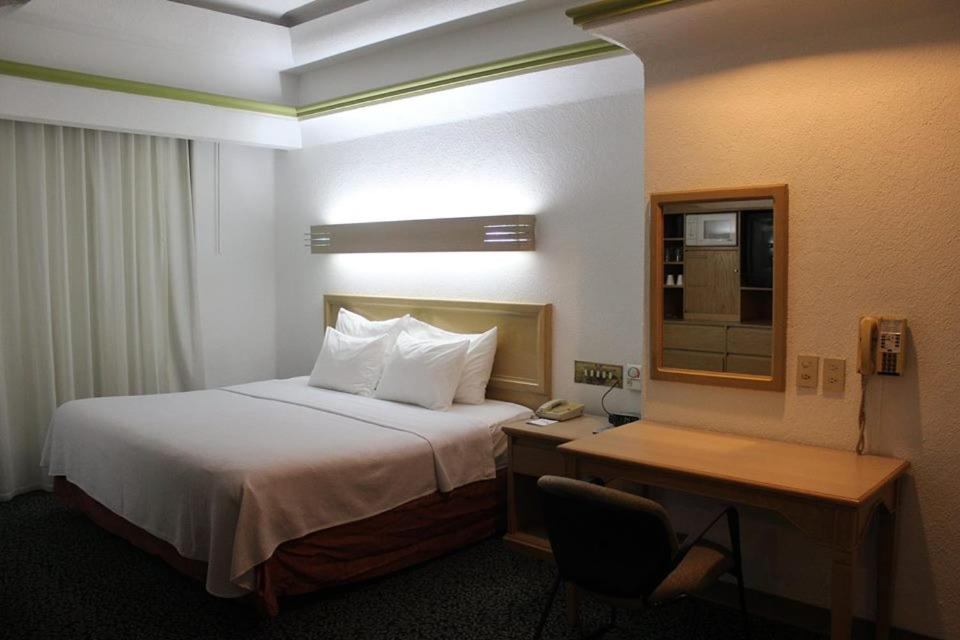 A bed or beds in a room at Hotel Monterrey Macroplaza