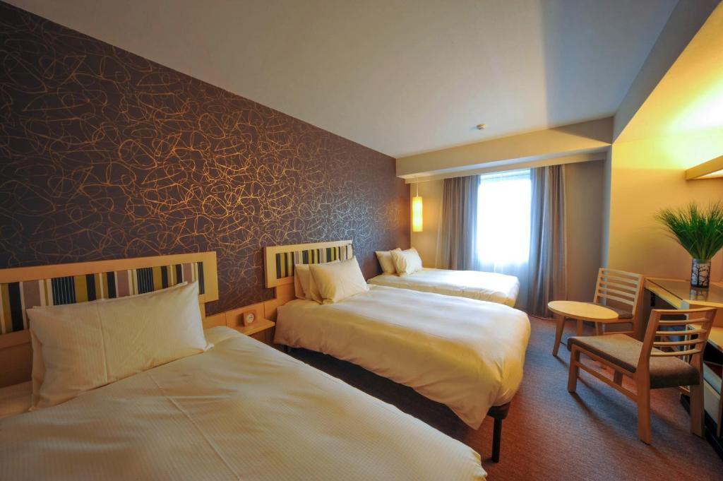 Un ou plusieurs lits dans un hébergement de l'établissement Hotel Resol Trinity Kanazawa