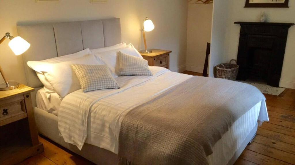 A bed or beds in a room at Denvir's Coaching Inn