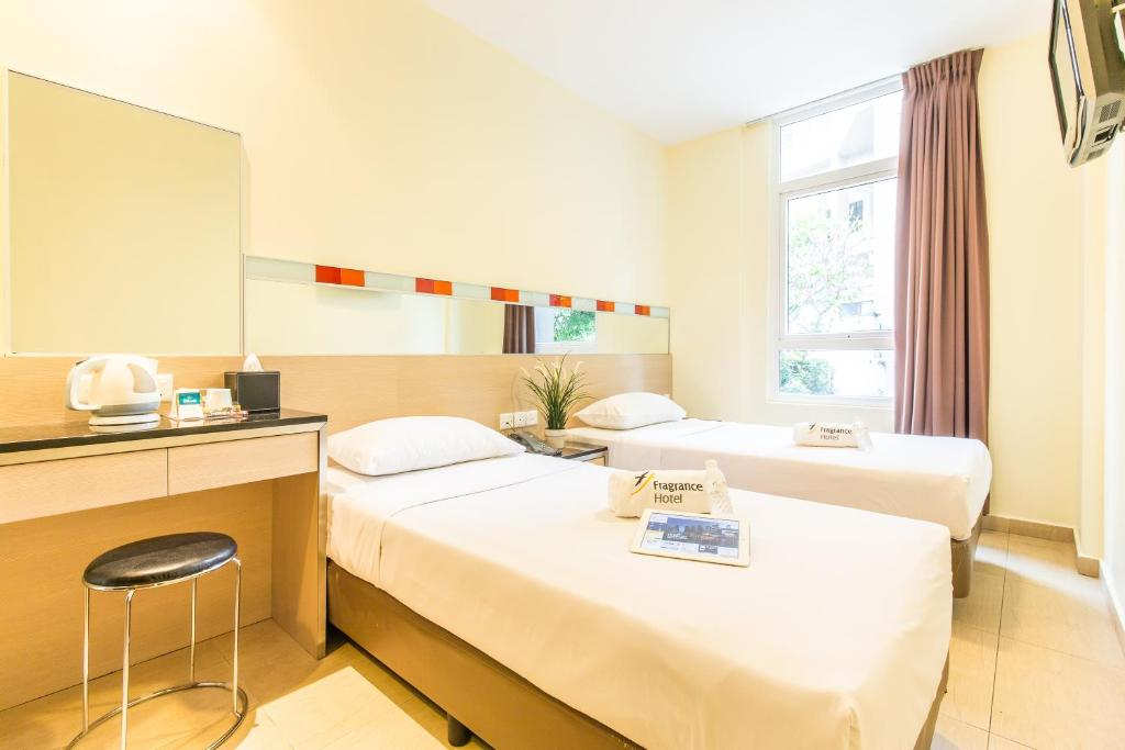 A bed or beds in a room at Fragrance Hotel - Oasis
