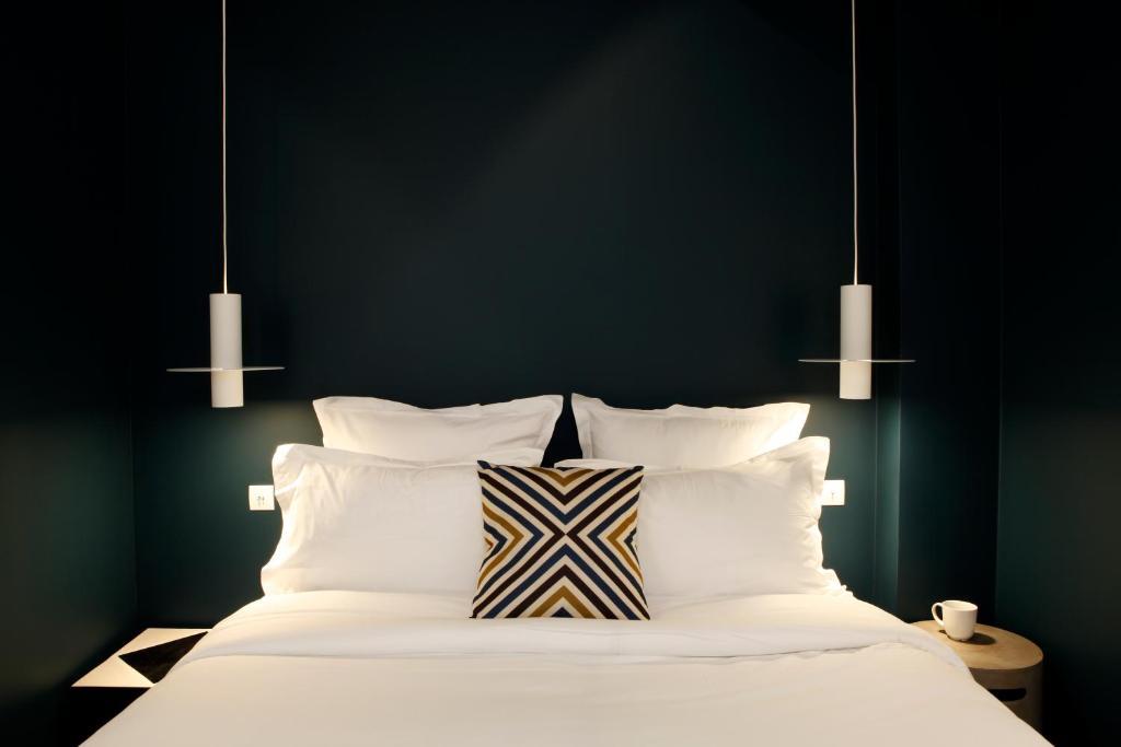 A bed or beds in a room at Hôtel Du Haut Marais