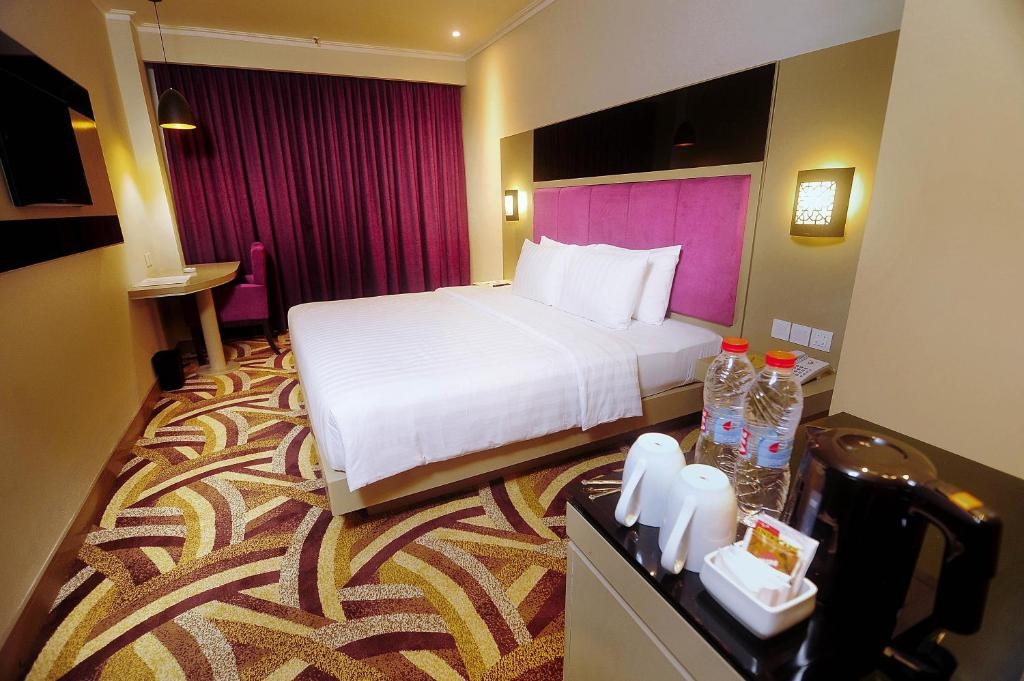 A bed or beds in a room at S-One Hotel Palembang
