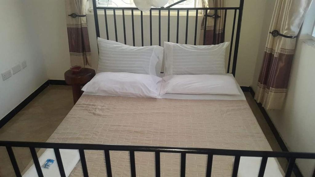 A bed or beds in a room at Entebbe Vine Inn