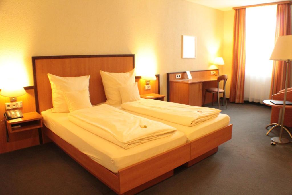 A bed or beds in a room at Hotel Blauer Wolf