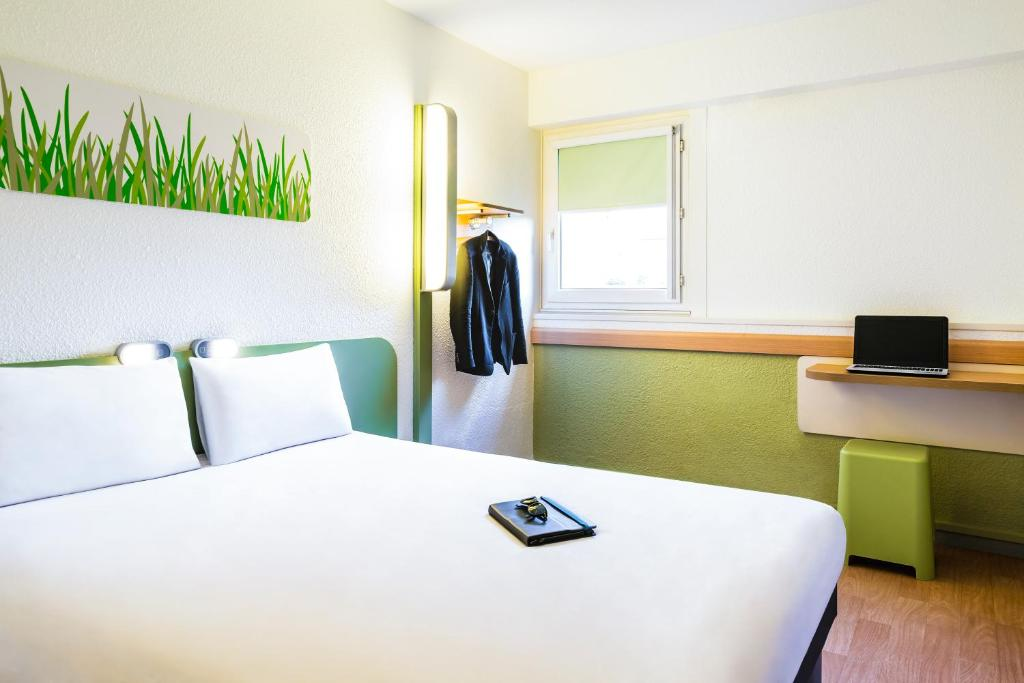 A bed or beds in a room at ibis budget Lyon Gerland