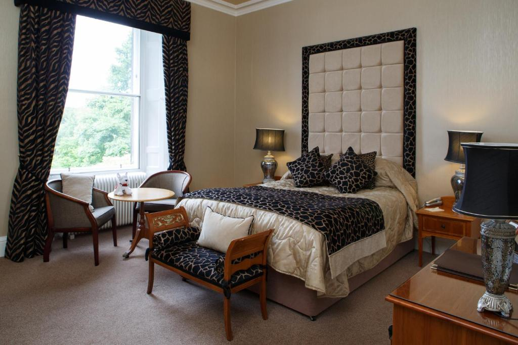 A bed or beds in a room at Garvock House Hotel