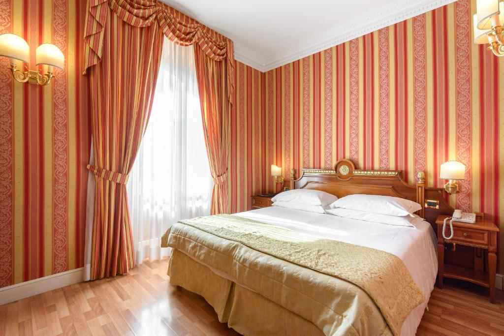 A bed or beds in a room at Gambrinus Hotel