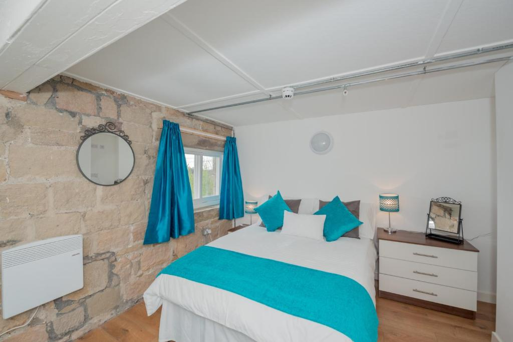 A bed or beds in a room at Benley City Stays - Kirkstall Bridge Apartments