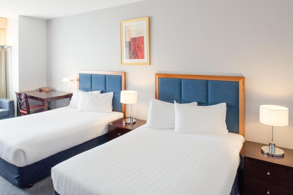 A bed or beds in a room at Seasons Of Perth