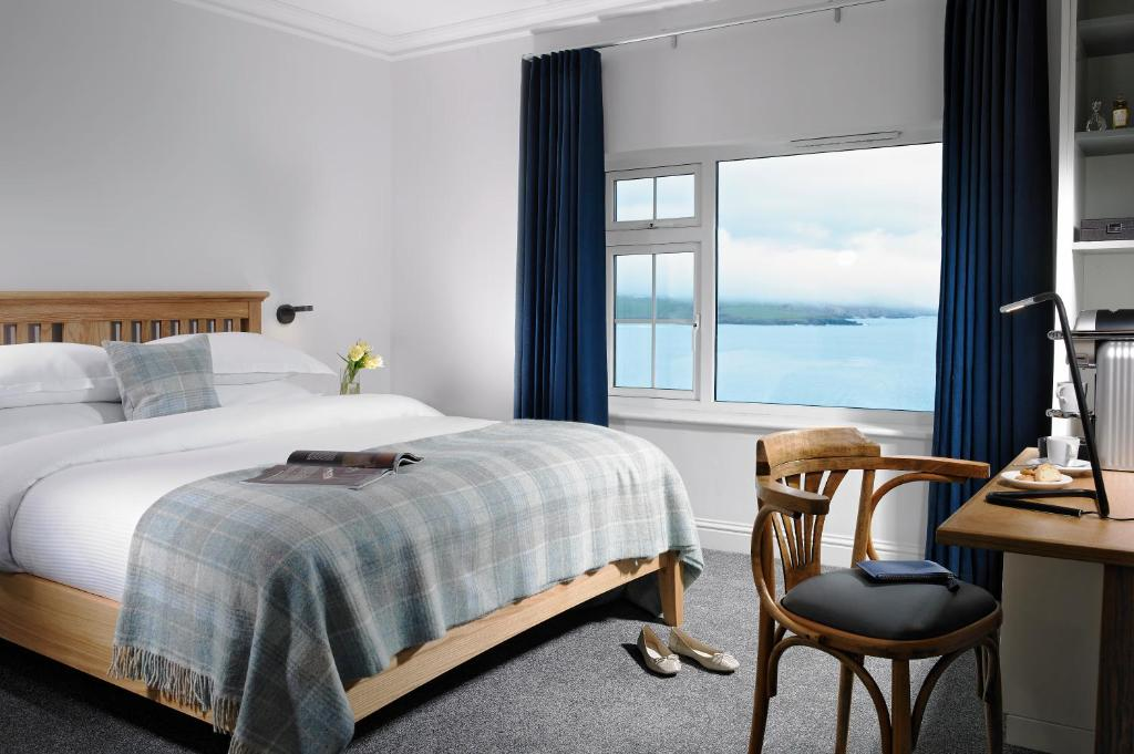 A bed or beds in a room at Dunmore House Hotel