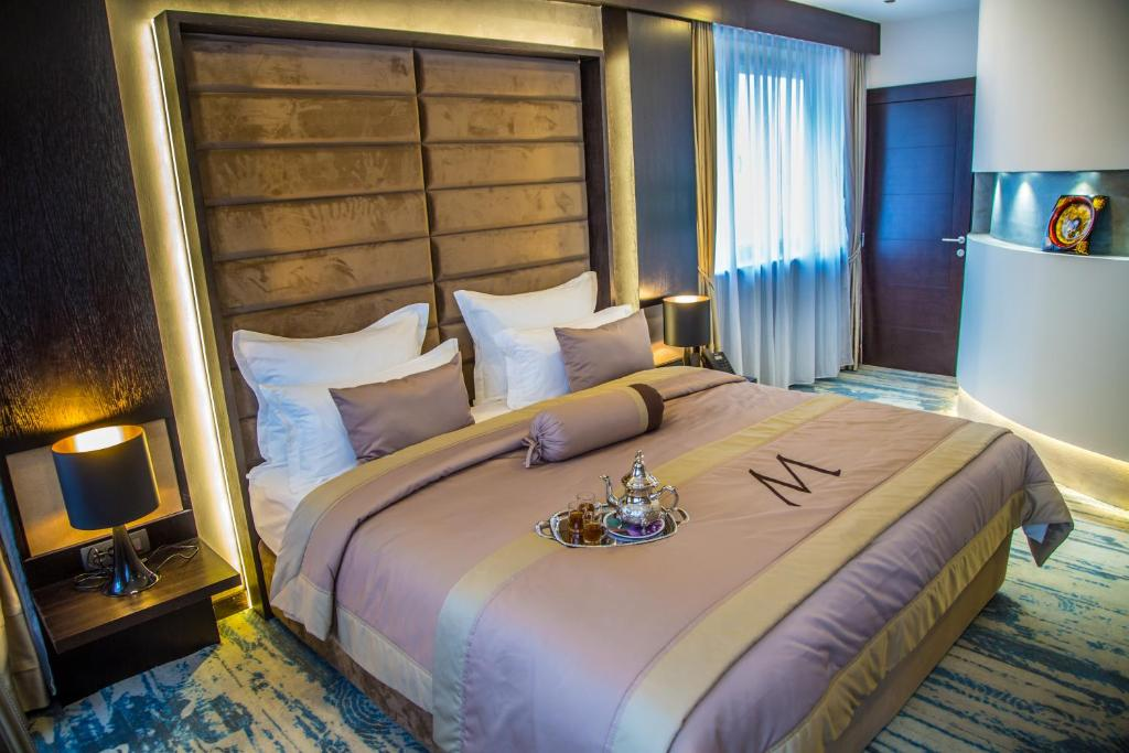 A bed or beds in a room at Malak Regency Hotel