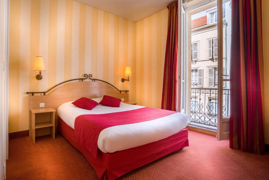 A bed or beds in a room at Hotel Delambre
