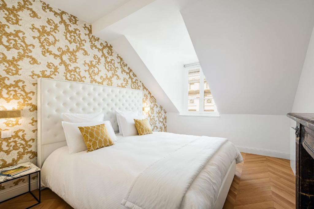 Een bed of bedden in een kamer bij Les Demoiselles à Versailles - Au Pied du Château