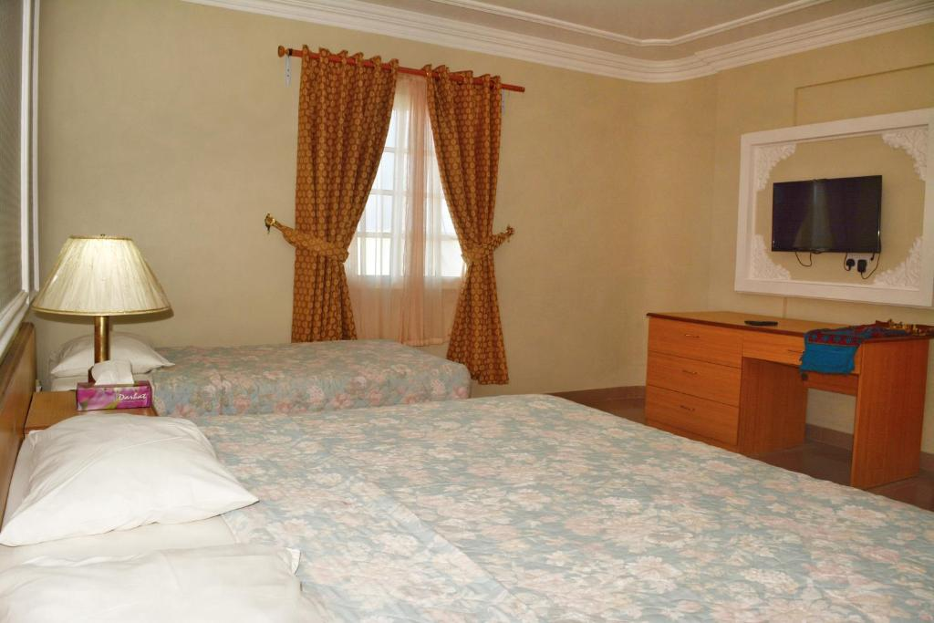 A bed or beds in a room at Darbat Hotel