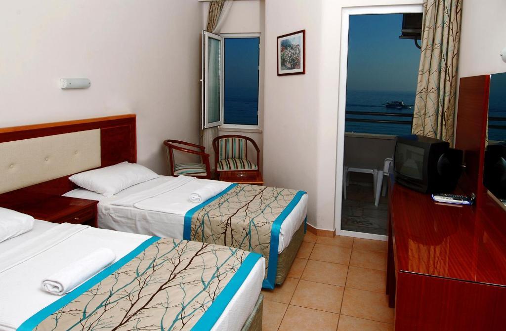 Кровать или кровати в номере Hatipoglu Beach Hotel