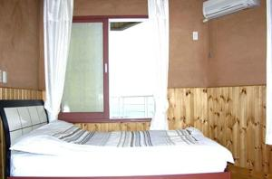 A bed or beds in a room at Jisakke Poongyeong Pension