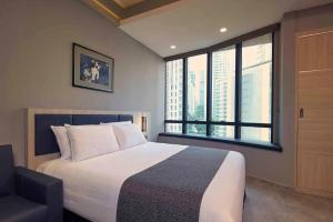 A bed or beds in a room at Orchard Grand Court