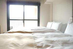 A bed or beds in a room at A Good Day Fukuoka Riverside