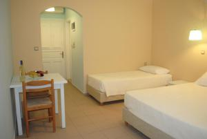 A bed or beds in a room at Apollonia Hotel