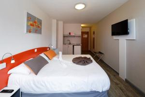 A bed or beds in a room at City Résidence Strasbourg Centre